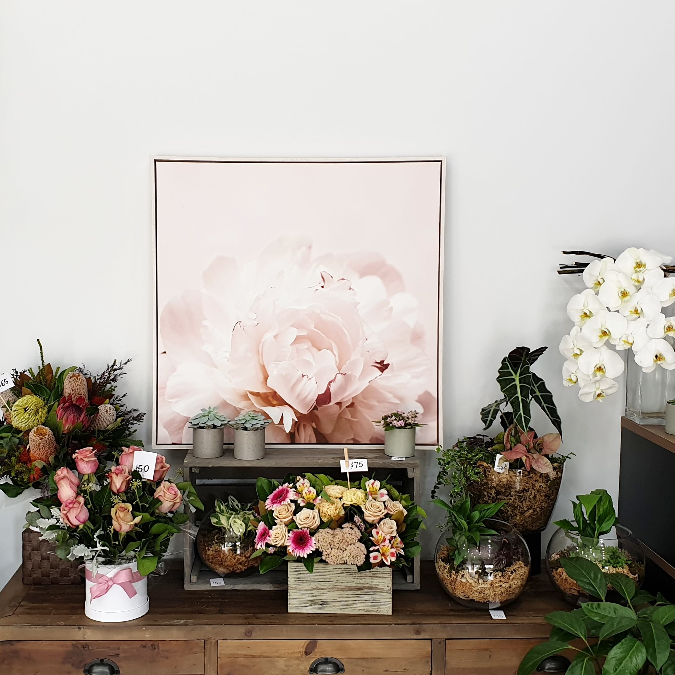 shop display, after, shows a painting of a peony and floral arrangements.
